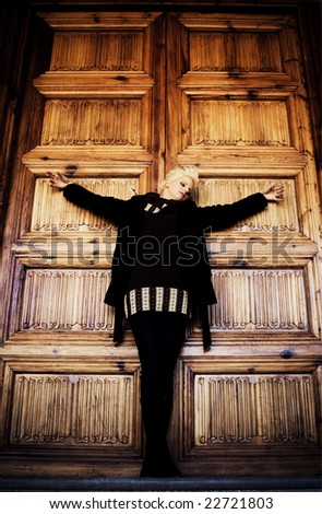 Young woman in casual clothing crucified in church wooden door. - stock photo
