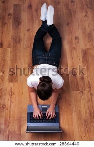 Young woman in casual clothing lying on a wooden floor using a laptop computer