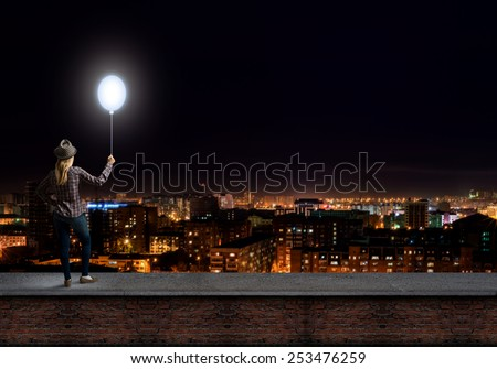 Young woman in casual holding balloon against night city - stock photo