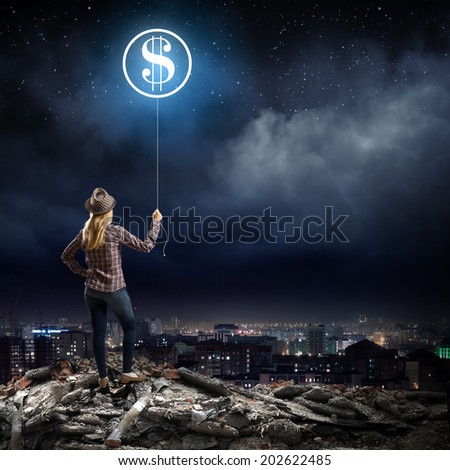 Young woman in casual holding balloon shaped like dollar - stock photo