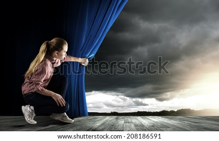 Young woman in casual opening blue curtain and looking at sky - stock photo