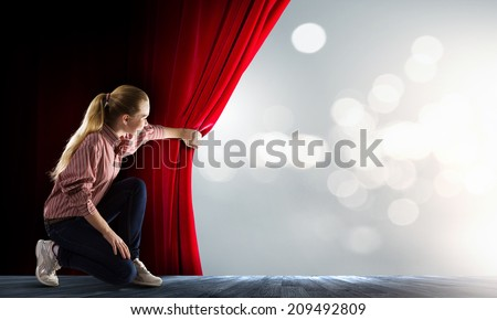 Young woman in casual opening red curtain - stock photo