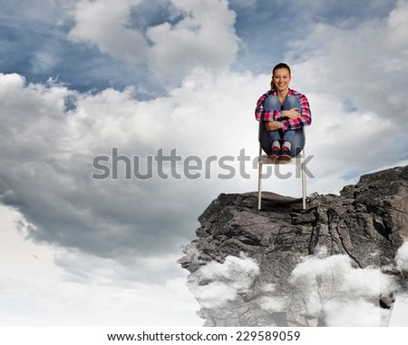 Young woman in casual sitting in chair on top of rock - stock photo