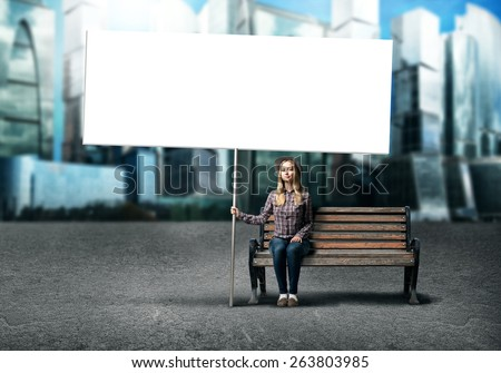 Young woman in casual sitting on bench with white blank banner - stock photo
