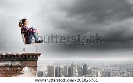 Young woman in casual sitting on in chair on top of building - stock photo