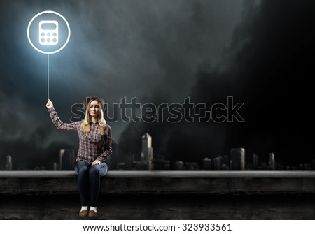 Young woman in casual sitting on roof and holding glowing balloon