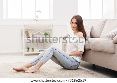 Young woman in casual sitting on the floor at home and looking at camera, copy space