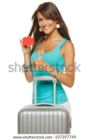 Young woman in casual standing with silver travel bag holding empty credit card and showing thumb up sign, isolated on white background
