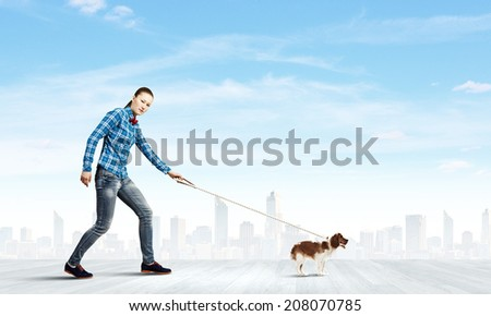 Young woman in casual walking with dog on lead - stock photo