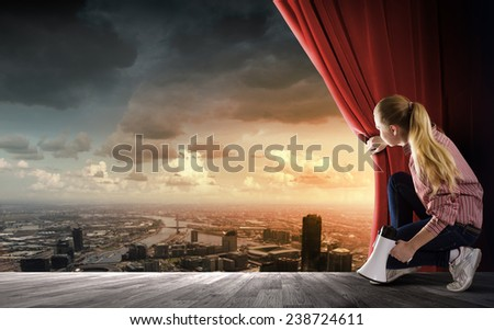 Young woman in casual with megaphone opening curtain - stock photo