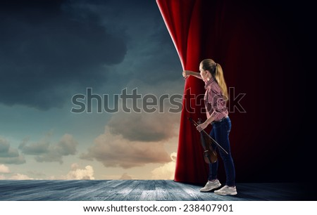 Young woman in casual with violin opening curtain - stock photo