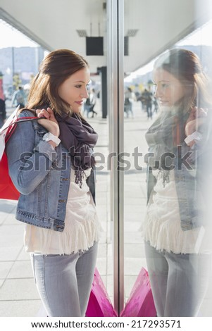 Young woman in casuals window shopping - stock photo