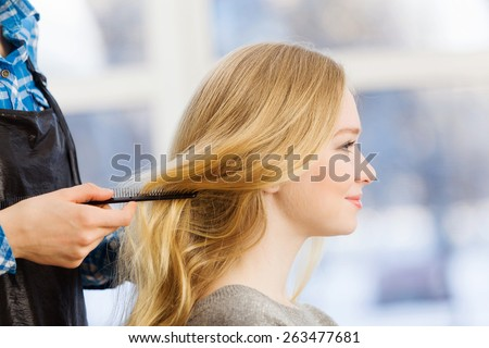 Young woman in chair at barbers and hairdresser - stock photo