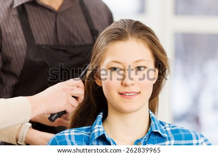 Young woman in chair at barbers and male hairdresser - stock photo