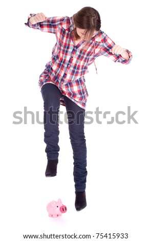young woman in checkered blouse breaking a piggy bank - stock photo