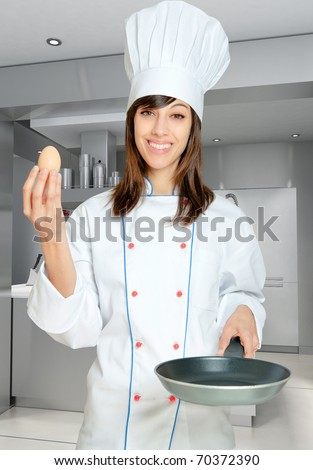 Young woman in chef?s  attire with an egg and a frying pan - stock photo