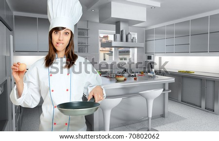 Young woman in chef?s  attire with funny expression with an egg and a frying pan