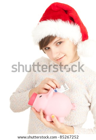 young woman in Christmas hat putting five euro in piggy bank