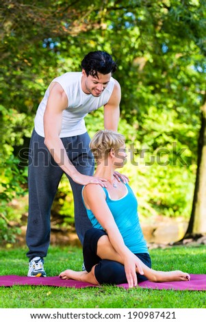 Young woman in city park doing yoga or warming up for exercising with her personal trainer or teacher - stock photo