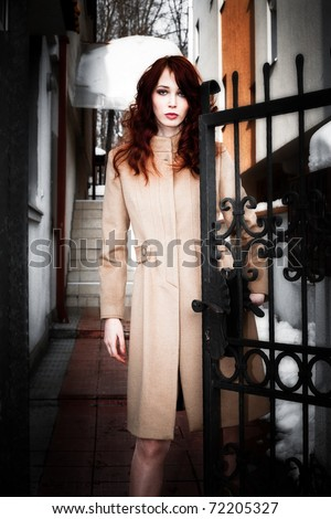 young woman in coat standing at entrance gate, serious face expression, outdoor, winter day