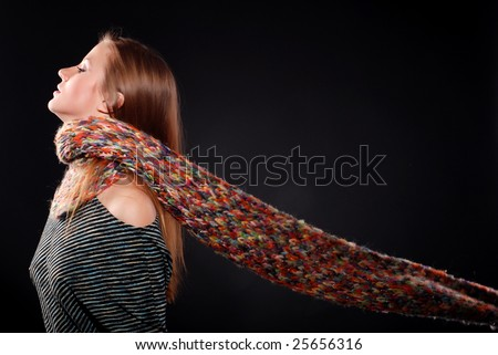 young woman in color wool scarf at black background - stock photo