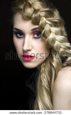 young woman in colorful art makeup and beautiful blonde braid
