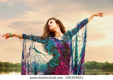 young woman in colorful dress dance in nature summer day small amount of grain added