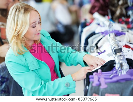 Young woman in colorful raincoat choosing clothes at shopping mall - stock photo
