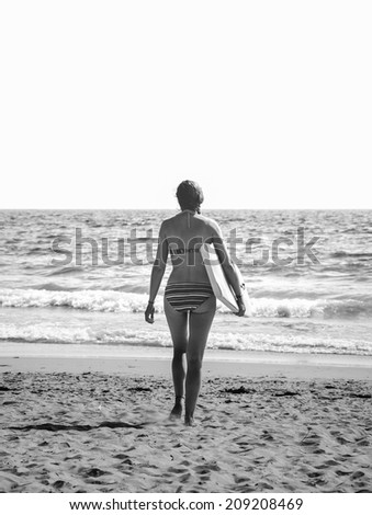 Young woman in colorful striped swimsuit  walking towards a water holding a surf board . Back view. (Brittany, France) Freedom concept. Aged photo. Black and white. - stock photo