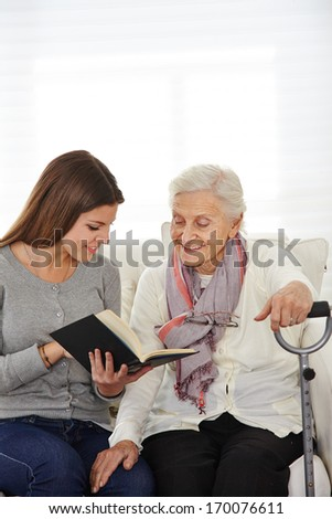 Young woman in community service reading books to senior citizens - stock photo
