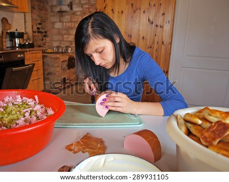 Young woman in country kitchen prepares boiled sausage for meat salad. - stock photo