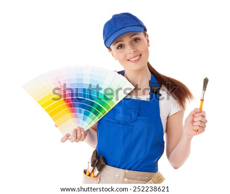 Young woman in  coverall with a color guide and paintbrushes on a white background. - stock photo