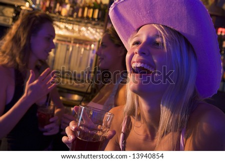 Young woman in cowboy hat laughing at a nightclub - stock photo