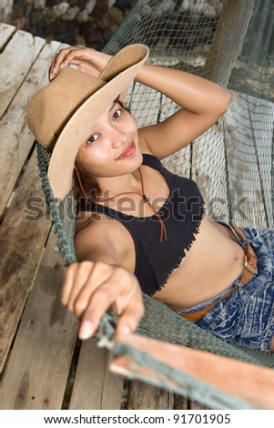 Young woman in cowboy hat resting on a hammock - stock photo