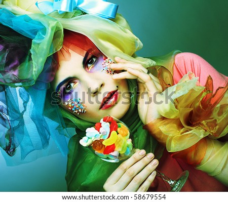 Young woman in creative cloth with sweets