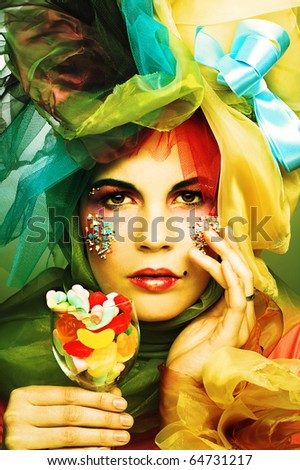 Young woman in creative cloth with sweets - stock photo