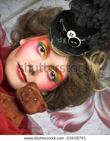 Young woman in creative image in little black hat and with toy