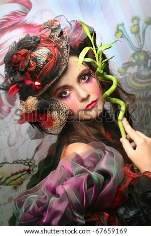 Young woman in creative image wint bamboo