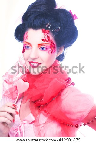 Young woman in creative image with sweet in her hands - stock photo