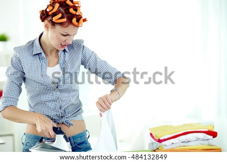 Young woman in curlers ironing clothes and looking at her watch in despair