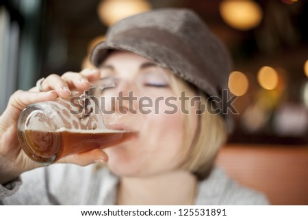 Young woman in cute brown hat drinking a beer. - stock photo