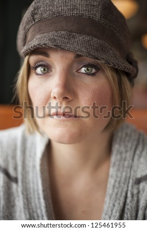 Young woman in cute brown hat staring straight ahead into the camera