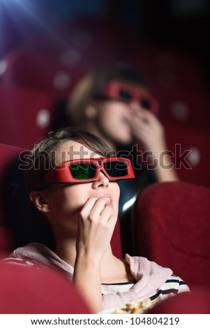 Young woman in 3D movie with popcorn - stock photo