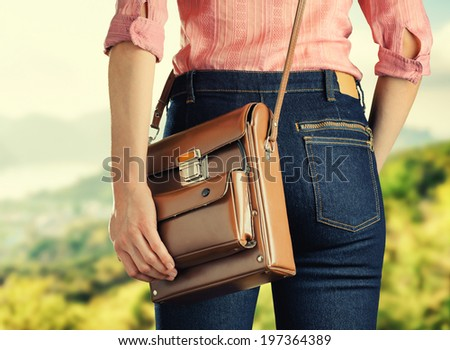 Young woman in deep blue jeans holding a bag. Retro style. - stock photo