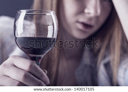 Young woman in depression, drinking alcohol. Focus on glass - stock photo