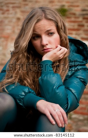Young woman in depression outdoors - stock photo