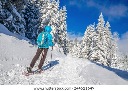 Young woman in down jacket hiking on snow shoes in cold winter scenery, Beskidy, Poland - stock photo