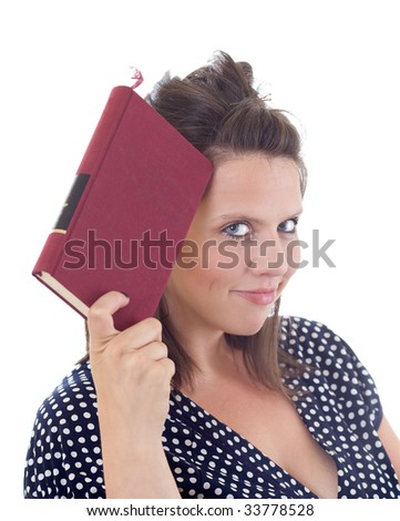 Young woman in dress holding a book to her head; isolated on a white background. - stock photo