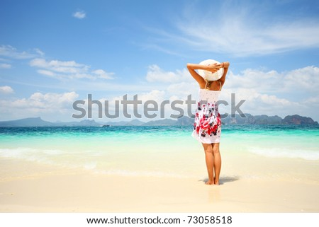 Young woman in dress holding a straw hat and looking to a blue sea - stock photo