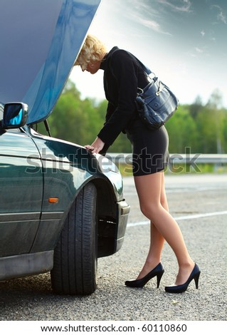 Young woman in dress near broken car - stock photo